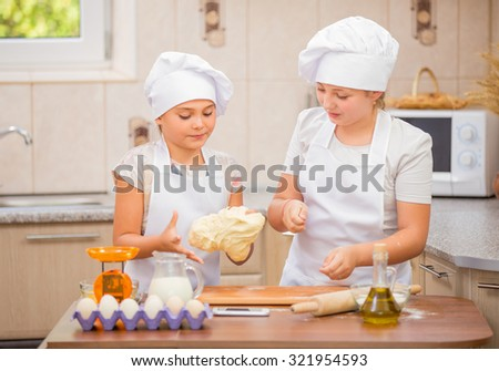 Two girls in costumes chefs prepare meals in the kitchen