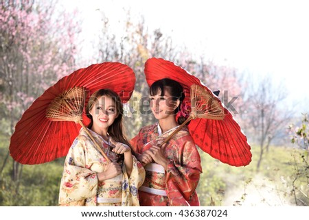 Two girls in kimonos acting are looking beautiful thing. - stock photo