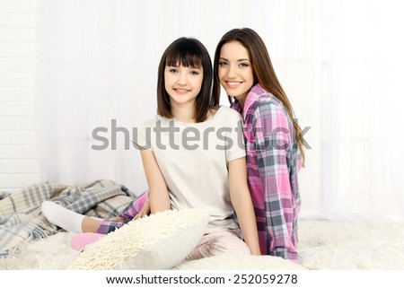 Two girls in pajamas sitting on fluffy white carpet, on light background - stock photo