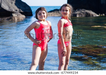 two girls in red swimsuits posing on the beach