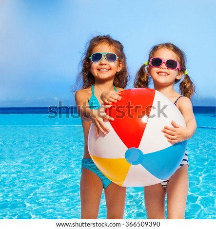 Two girls in swimwear with big inflatable ball - stock photo