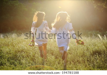 two girls in the national Ukrainian clothes with wreaths of flowers in their hands running over the grass - stock photo