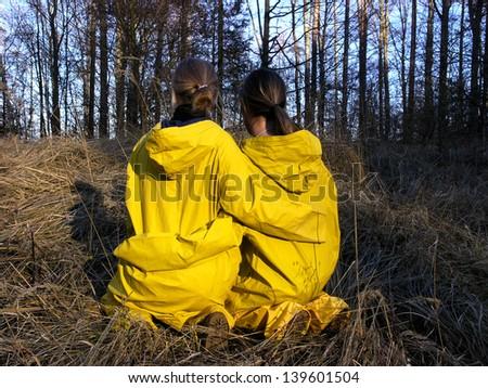 Two girls in yellow raincoats - stock photo