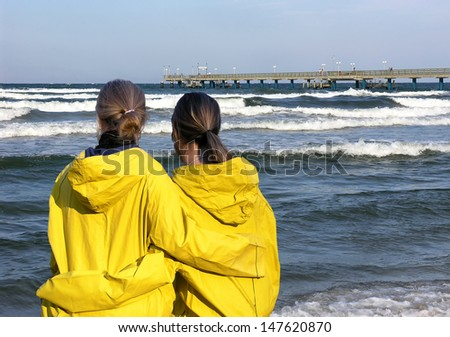 Two girls in yellow raincoats on a coast - stock photo