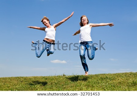 Two girls jump on a green grass against the blue sky