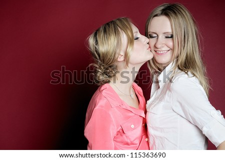two girls kiss in red background