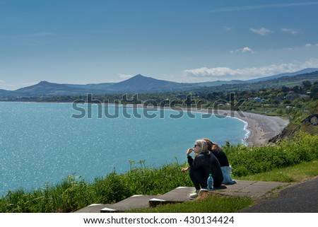 two girls ladies teenagers sitting at top of the hill watching sea ocean mountains hope for the future - stock photo