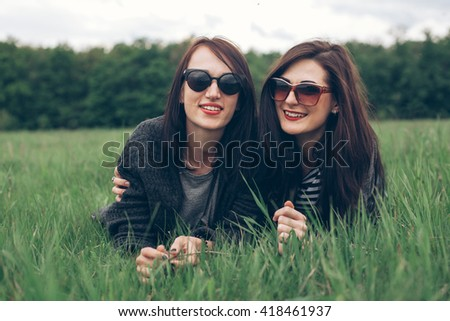 Two girls lie on the grass and smiling. Best friends