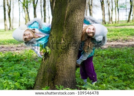 two girls look out because of a tree - stock photo