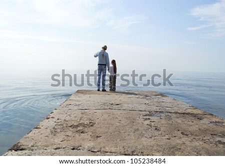 Two girls looking away from the ocean pier - stock photo