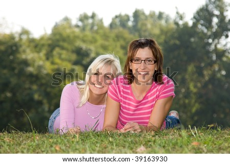 two girls lying in the park - stock photo