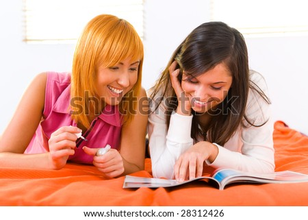 Two girls lying on bed and browsing magazine. One of them painting her nails. Front view.