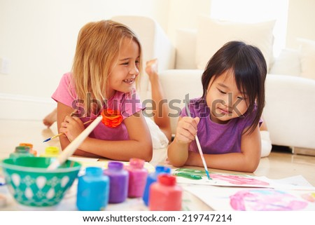 Two Girls Lying On Floor And Painting Picture At Home - stock photo