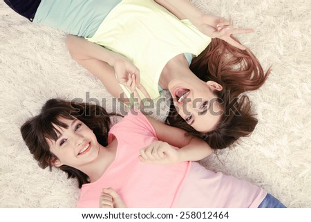Two girls lying on fluffy white carpet, top view - stock photo