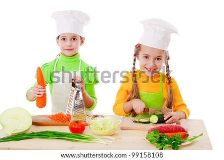 Two girls make a vegetable salad, isolated on white