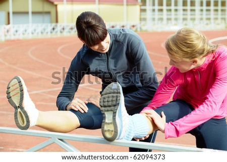Two girls making exercises in the stadium - stock photo