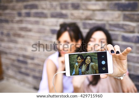 Two Girls making selfie Outdoors against brick wall
