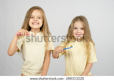 Two girls of four and six years of brushing their teeth toothbrushes
