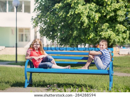 two girls on bench in park - stock photo