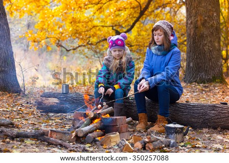 Two girls on picnic in the autumn forest sitting around the campfire - stock photo