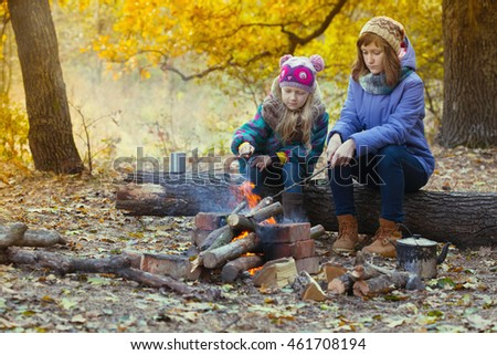 Two girls on picnic in the autumn forest sitting around the campfire