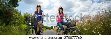 Two girls on summer bicycle trip in country - stock photo