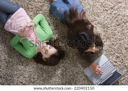 Two girls on the floor with MP3 player and laptop - stock photo