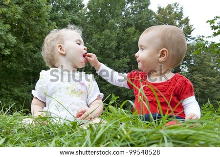 Two girls on the meadow feed each other - stock photo