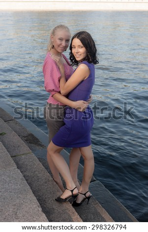 Two girls on the steps near the water