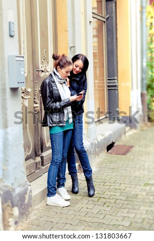 Two girls on the street use a cell phone