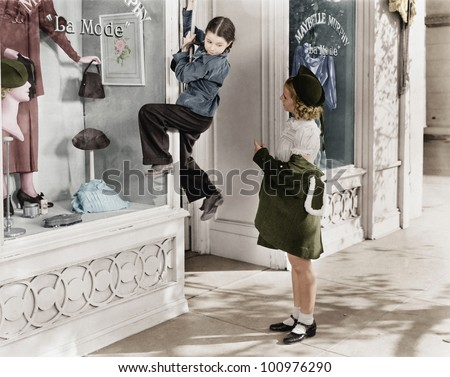 Two girls on the street with one climbing on a display window - stock photo