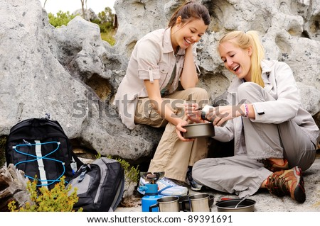 two girls open a can of baked beans while they rest from trekking in the wilderness - stock photo