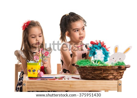 Two girls painting Easter eggs and making decorations at table - stock photo
