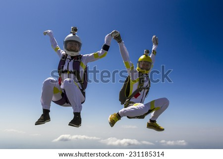 Two girls parachutists in free style. - stock photo