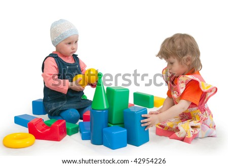Two girls play cubes on a white background - stock photo
