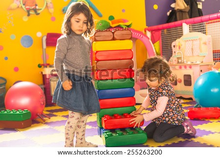 Two girls play with big bricks in playroom - stock photo
