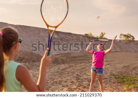 two girls playing badminton outdoor - stock photo