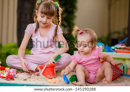 Two girls playing in a sandbox - stock photo