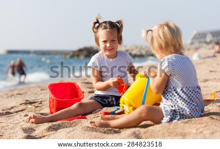 two girls playing on  beach - stock photo