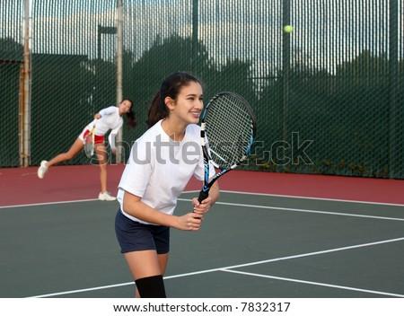 Two girls playing tennis - stock photo