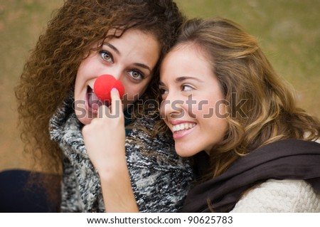 Two girls playing with clown nose