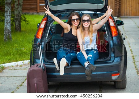 Two girls posing in car. Resting in the country. taking a trip somewhere by car