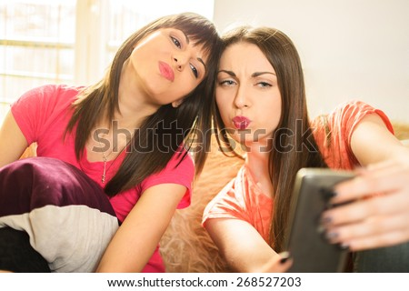 Two girls pouting while taking a selfie photo on mobile phone.