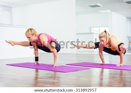 Two girls practicing toga, Tittibhasana/Insect or Firefly Pose