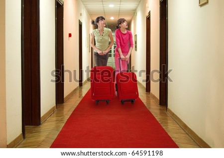 Two girls push luggage in hotel hall and looking at number of rooms - stock photo