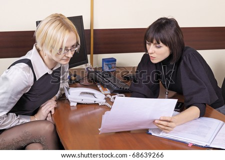 Two girls read documents at office behind a table