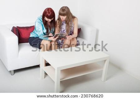 two girls reads magazine - stock photo