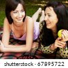 two girls relaxing in park  on blanket - stock photo