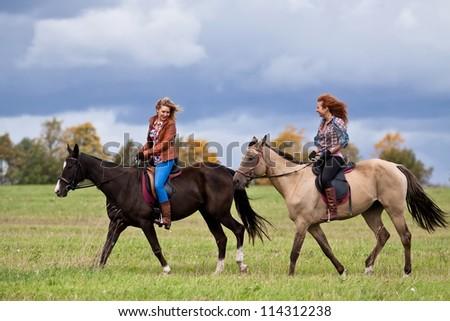 Two girls ride beautiful Akhal-Teke horses - stock photo