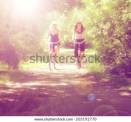 two girls riding bikes on a path in a park full of trees done with a retro vintage instagram filter - stock photo